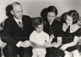 Lister Hill looking at a newspaper with his wife and children.