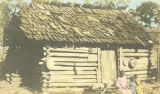 Three African American children in front of a cabin.