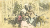 African American woman with three children and a dog.
