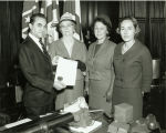 Governor George Wallace presenting a certificate to three women in his office.