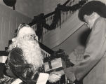 George Wallace dressed up as Santa Claus,  handing a gift to an African American man at the...