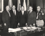 Governor John Patterson and four other men standing around the governor's desk.