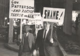 White and African American protesters carrying signs at a demonstration against Patterson and...
