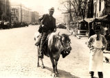 African American man riding bull on Madison Avenue in Montgomery, Alabama.