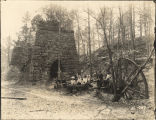 Group of men and women seated in front of a Tannehill Ironworks furnace in Jefferson County,...