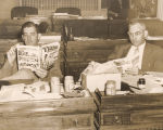 Senators Graham Wright and Albert Patterson taking a break at their desks during a legislative...
