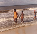 African American woman and boy walking in the waves along the beach at Gulf Shores, Alabama.