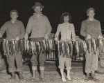 Three men and a woman holding a long line of green trout caught by five fishermen in the Mobile...