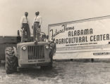 Men on a construction vehicle in front of a billboard advertising the coming Alabama Agricultural...