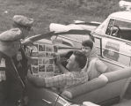 Two Alabama Highway Patrol officers looking over a tourism brochure with a man and woman in a car.