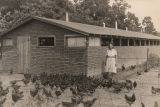 Woman in front of a chicken house in or near Decatur, Alabama.