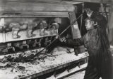 Worker at a reduction pot at the Reynolds Metal Company plant in Listerhill, Alabama.
