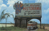 "Train of the ""Alabama & Historama Railway Co."" passing under the billboard for the..."