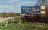 "Children standing beside a billboard that reads, ""Welcome to Alabama. John Patterson,..."