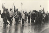 Martin Luther King, Jr., Coretta Scott King, James Bevel, and others walking in the rain during...