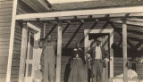 African Americans standing on a porch in Lee County, Alabama.
