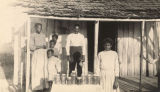 African American family standing around a display of preserves in front a cabin in Pickens County,...