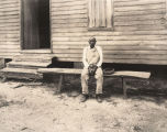 African American man sitting in front of a wooden church building in rural Tuscaloosa County,...