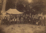 Group of men holding guns, gathered in front of a tent after a hunt.