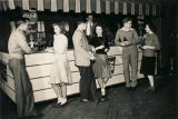Teenagers drinking soft drinks at a refreshment booth in a youth club in Alabama.