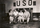 Two couples drinking soft drinks on a bench at the USO Club in Talladega, Alabama.