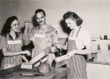 Two women and serviceman in the kitchen at the USO club in Talladega, Alabama.