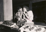 Serviceman and a young woman sharing a soft drink at the USO club in Talladega, Alabama.