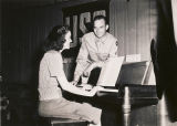 Serviceman listening to a young woman play a piano at the USO club in Talladega, Alabama.