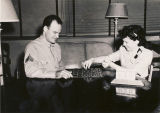 Serviceman and young woman playing checkers at the USO club in Talladega, Alabama.