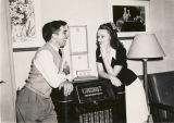 Young man and woman listening to the radio at the USO club in Talladega, Alabama.