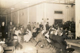 Servicemen and guests sitting and standing in groups, probably during a dance at the USO club in...