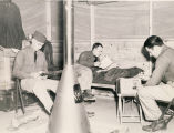 Three servicemen in a barrack in Alabama.