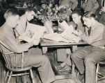 Servicemen reading newspapers at a USO club in Alabama.