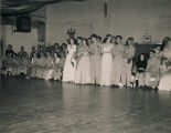 Servicemen and young women watching a floor show during a formal dance at the USO club in...