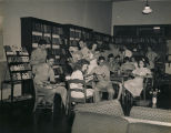 Servicemen and young women in the reading room at the USO club in Montgomery, Alabama.