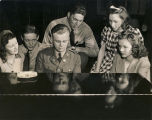 Servicemen and young women gathered around a piano at a USO club in Alabama.