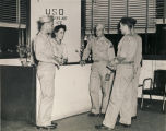 Servicemen and young woman at the front desk of a USO club in Alabama.