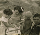 Young woman reading to three children from a housing project in Mobile, Alabama.