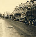 American military trucks lined up along a road in western Europe.