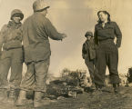 Harriett Engelhardt with three American soldiers, standing by a fire in a field in Germany.