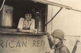 Young woman giving coffee to a soldier from an American Red Cross Clubmobile.