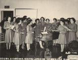 Servicewomen singing around a piano at the opening of the Maxwell Field Service Club in...