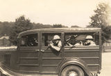 Four MPs of the New York National Guard aiming guns from inside a Military Police vehicle at Camp...