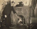 Speaker of the House William Bankhead placing a log in the fire in the Speaker's office in...