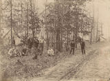Group of young men at a camp in the woods.