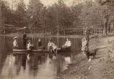 Group in a boat and on the shore at a lake or pond.