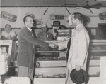 John Patterson shaking hands with a man in a butcher's shop during the 1958 gubernatorial campaign.