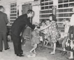 John Patterson shaking hands with a young girl outside a store during the 1958 gubernatorial...