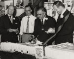 Governor John Patterson with three men, having cake in front of a display of Alabama Beauty flour.