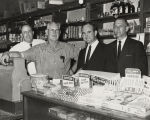 John Patterson with several men behind the counter of a general store.
